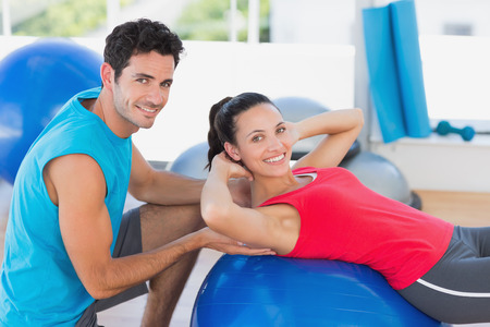 man looking out: Portrait of a male trainer helping woman with her exercises at a bright gym