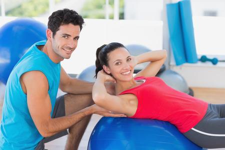 hombre flaco: Retrato de una mujer entrenador de ayudar a hombres con sus ejercicios en un gimnasio brillante Foto de archivo