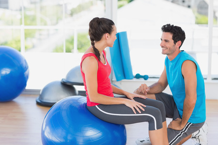 Side view of an instructor and woman with exercise ball at a bright gym