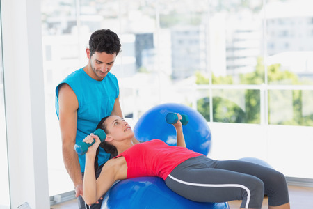 Male trainer helping woman with her exercises at a bright gym photo