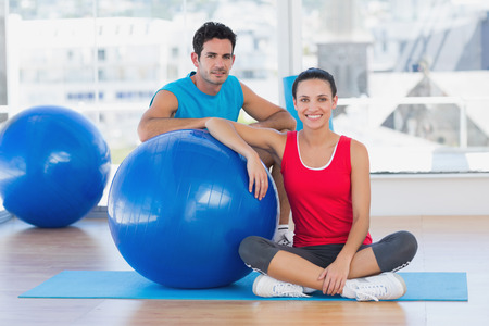 Portrait of an instructor and smiling woman with exercise ball at a bright gym photo