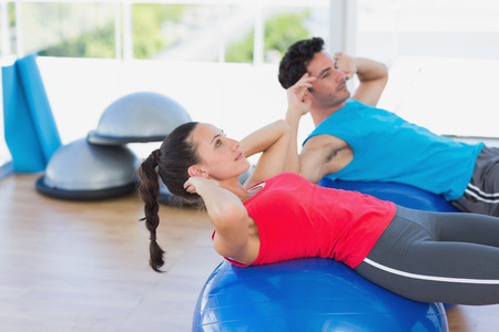 Side view of a fit young couple exercising on fitness balls at a bright gym photo