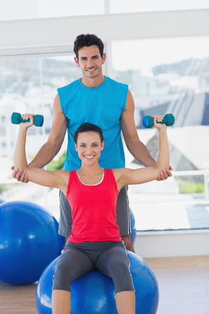 Portrait of a male trainer helping woman with her exercises at a bright gym photo