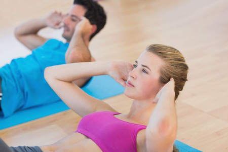 sit ups: Side view of a determined young couple doing sit ups at a gym Stock Photo