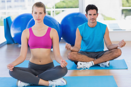 Full length portrait of a young couple sitting in lotus posture at fitness studio photo