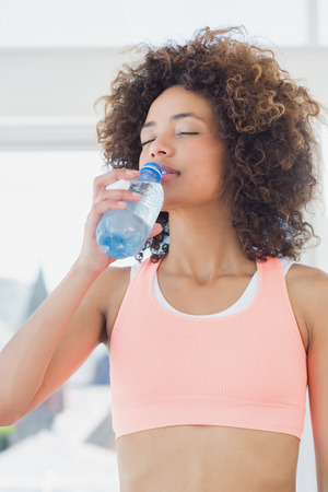 water activity: Fit young female drinking water at a bright gym Stock Photo