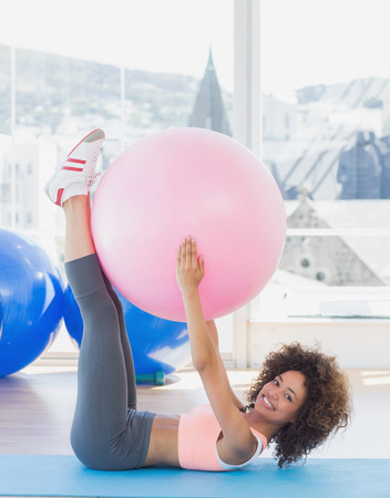 Side view of a sporty young woman with exercise ball in the fitness studio photo