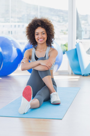 Full length portrait of a fit young woman sitting on exercise mat in a bright fitness studio Stock Photo