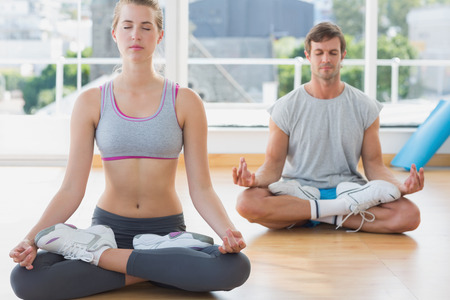 Sporty young couple in meditation pose with eyes closed at fitness studio photo