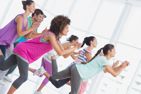 Fitness class and instructor doing pilates exercise in a bright room