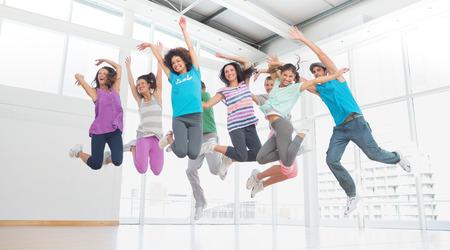 třída: Fitness třídy a instruktor dělá pilates cvičení ve světlé místnosti