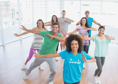 Fitness class and instructor doing pilates exercise in a bright room photo