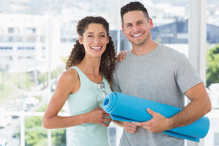 standing water: Portrait of happy couple holding water bottle and exercise mat at gym Stock Photo