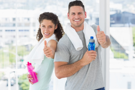Portrait of happy couple with water bottles gesturing thumbs up at gym photo