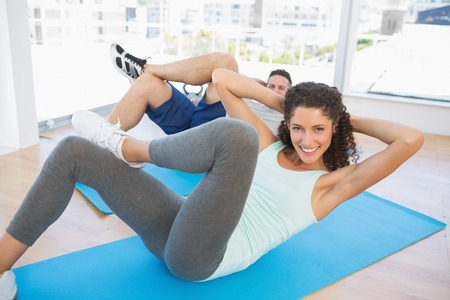 sit ups: Portrait of fit couple doing sit ups in fitness studio Stock Photo