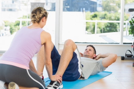 Female trainer assisting fit man in doing sits up at gym