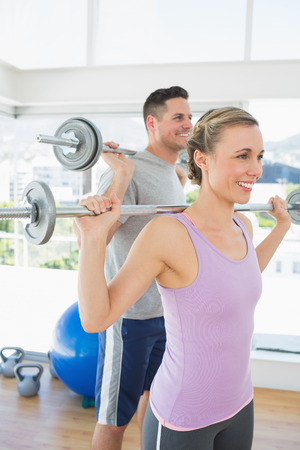 woman lifting weights: Happy fit woman and man lifting weights at exercise room