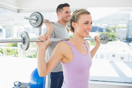 happy fit woman and man lifting barbells in the exercise room photo
