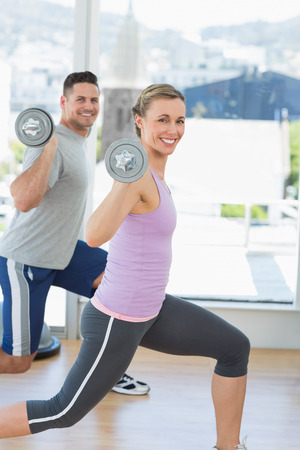 Side view portrait of happy woman and man exercising with barbells at gym photo