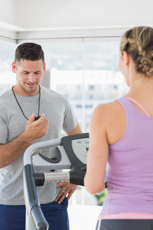 Woman exercising on treadmill and being timed by a personal trainer at gym photo