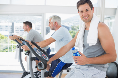 Portrait of fit man on exercise bike holding water bottle at gym photo