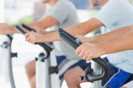 Cropped image of men using exercise bikes at fitness studio photo