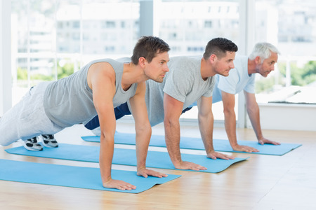 Three men doing push ups at fitness studio photo