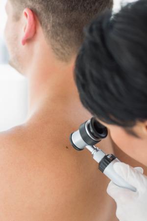 scrutinize: Female doctor examining melanoma with dermoscope on back of man