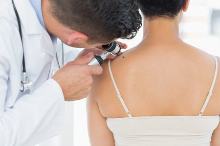 dermatologist: Male dermatologist examining mole on back of woman in clinic Stock Photo