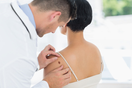 Male doctor examining mole on back of woman in hospital Stock Photo