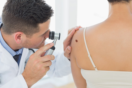 dermatology: Male doctor examining mole on back of woman in clinic