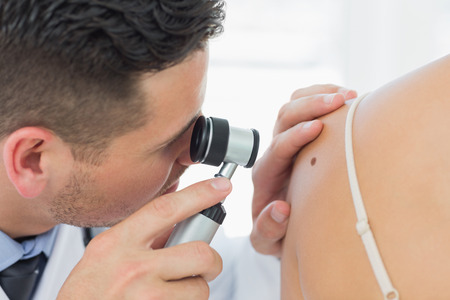 dermatology: Closeup of male dermatologist checking mole on woman in clinic