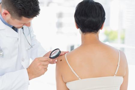 병원에서 돋보기 여자 피부과 검사 흑색 종