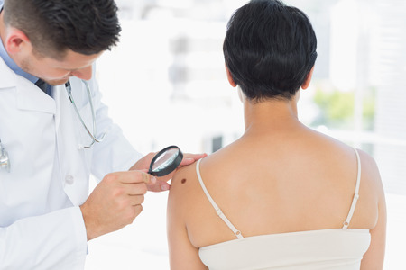Dermatologist examining melanoma on woman with magnifying glass in clinic