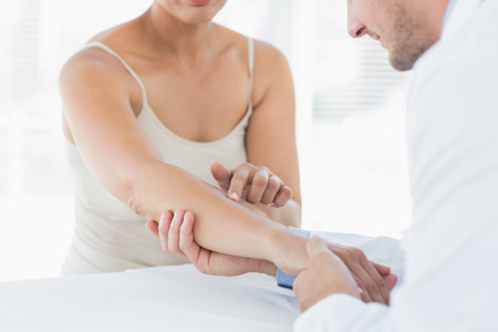 Mid section of male physiotherapist examining hand of woman in clinic photo