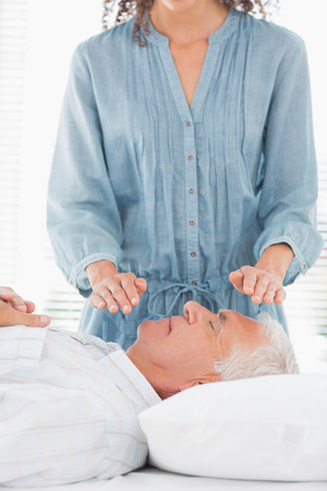 Female therapist performing Reiki over face of senior man at health spa photo
