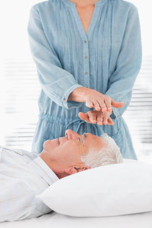 Female therapist performing Reiki over forehead of senior man at health spa photo