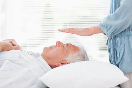 Massage therapist performing Reiki over senior man at health spa photo