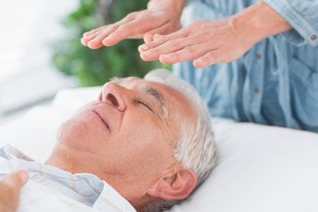 Massage therapist performing Reiki over senior man at health spa photo