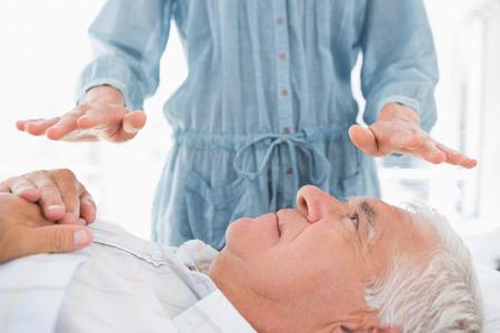 Senior man receiving Reiki treatment by massage therapist at spa photo