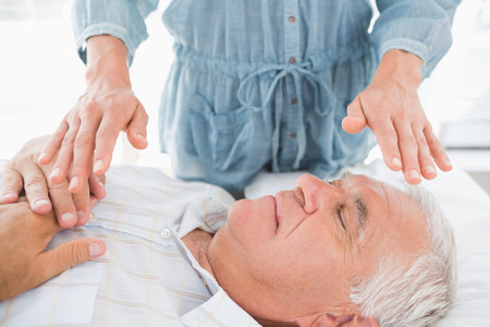 Senior man having Reiki treatment by massage therapist at spa Stock Photo - 27119896