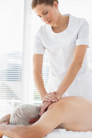 Female massage therapist massaging back of senior man in clinic photo