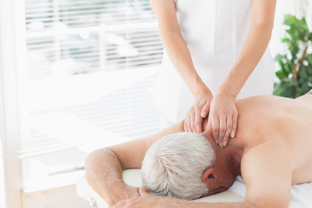 Senior man getting back massage in medical office photo