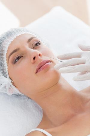 recieving: Beautiful young woman recieving botox injection in hospital