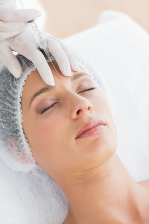 recieving: Closeup of beautiful woman recieving botox injection in forehead Stock Photo