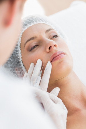 recieving: Closeup of beautiful woman recieving botox injection in upper lip