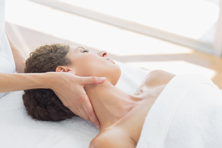 Beautiful young woman receiving neck massage in health spa photo