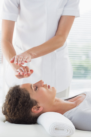 Female therapist performing Reiki over woman at spa photo
