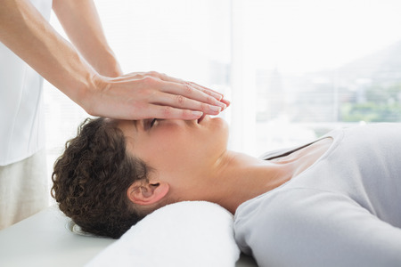 Attractive young woman having reiki treatment over face in health spa photo