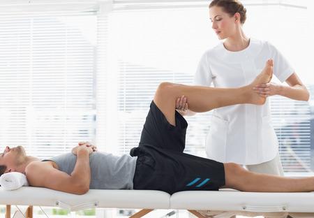 fisico: Fisioterapeuta masaje de la pierna del hombre joven en el spa